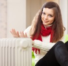 19528649 - smiling woman warms hands near radiator at home