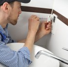 58950414 - a electrician changing a socket outlet in bathroom